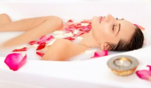 8740-woman-laying-in-milk-bath-with-rose-petals